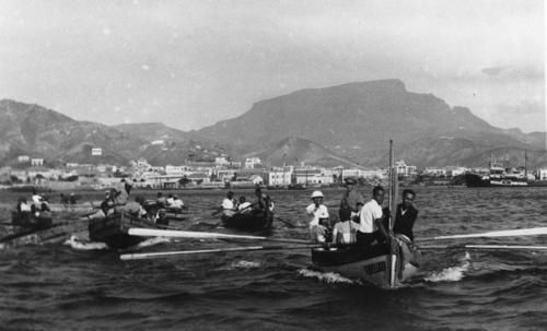 Fotografia de 1944, de autoria de Foto Melo. <BR> <BR>Embarque do Dr. Baptista de Sousa. <BR> <BR>De pé na popa da embarcação, a figura do Médico, vendo-se na sua esteira os inúmeros botes que o quiseram acompanhar até ao barco que o levou de volta a Portugal. <BR> <BR>Em boa hora se resolveu dar o nome de Baptista de Sousa, ao Hospital de Mindelo. <BR> <BR>Mantenhas | djomartins