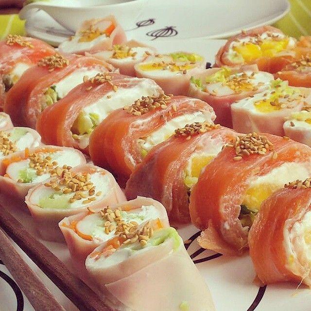 Makis impostores (sushi #dukan): corta un rectángulo de film de plástico de unos 20 cms. Base de los rolls, unos salmón ahumado y otros 2 lonchas superpuestas de jamón york. Pon en un extremo de cada roll queso de untar light y luego pimientos del piquillo, palito de cangrejo y lechuga. Lo enrollamos a modo de caramelo y se pone en el congelador durante unos 20 -30 min para poderlos cortar sin que se desmonten.
