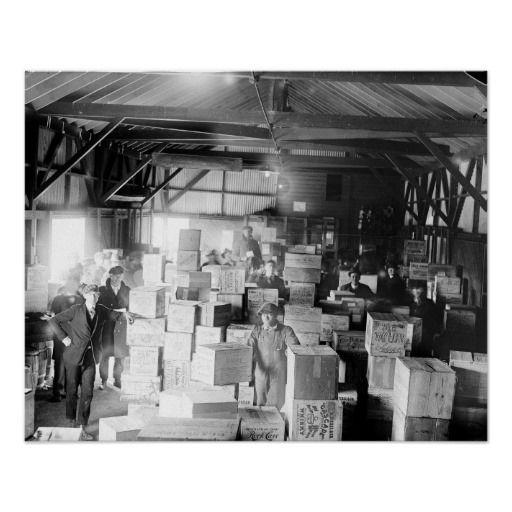 Bootleg Whiskey Warehouse, 1920. A group of men posing inside a warehouse full of bootleg whiskey during the Prohibition Era.