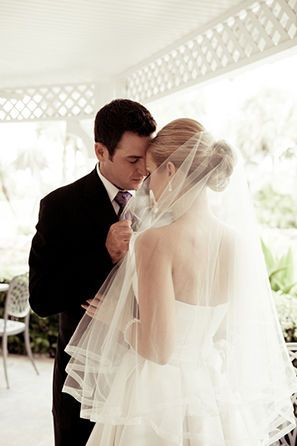 Bride wearing a fingertip veil and dancing with groom