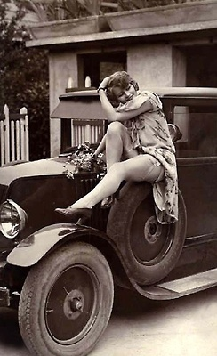 1920s pin up girl poses on a car