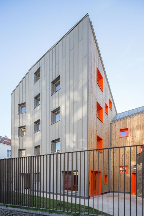 Bold orange windows punctuate the wooden facades of this angular apartment block that French studio Vous Êtes Ici Architectes has slotted between the existing buildings of a south Paris neighbourhood.