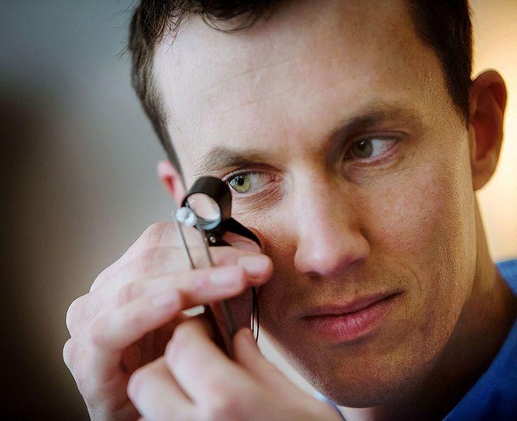 Engagement ring designer, diamond expert and handmade jeweller Julian Bartrom examining and brilliant cut diamond