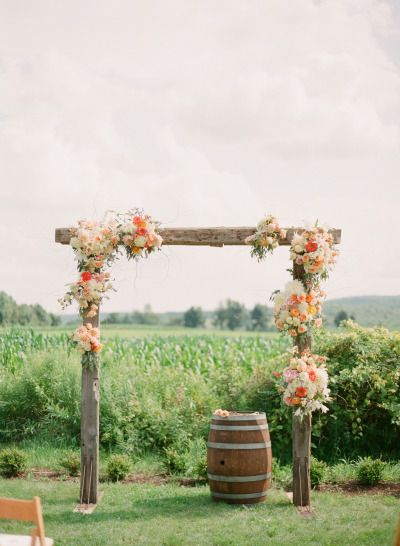 Rustic ceremony: wooden posts with roses and eucaplyptus and peonies and poppies for an outdoor outside boho bohemian gypsy wedding theme  http://www.stylemepretty.com/2015/05/26/rustic-elegant-ithaca-farm-wedding/ | Photography: Caroline Frost - http://carolinefrostphotography.com/