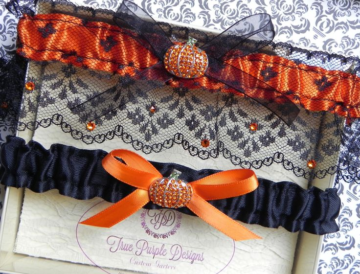 This elegant Halloween/Autumn themed garter set is made with silky orange satin overlaid with fine black lace. It is finished off with a sheer black bow and a sparkly orange rhinestone pumpkin. The la