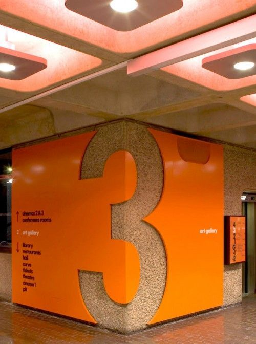 "The large ""3"" cut out, along with the bright orange color and the large square light fixtures in the ceiling catches people's attention and conveys necessary information.  At the Barbican Center in London and designed by Cartlidge Levine.:"