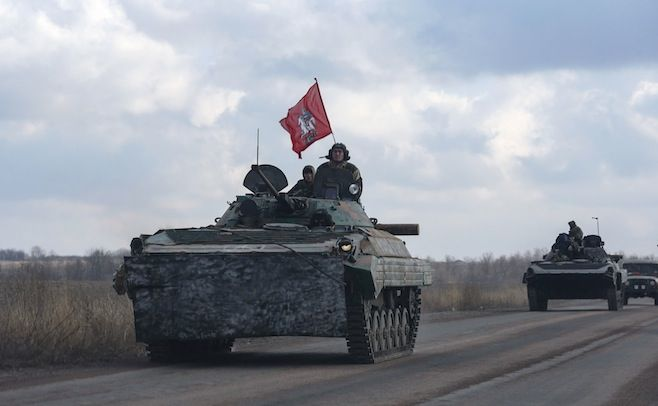 Maxim Shemetov / Reuters Members of the separatist self-proclaimed Donetsk People's Republic drive armoured vehicles, with Saint George slaying the Dragon displayed on a red flag, near Yenakiieve, Donetsk region, Feb. 4, 2015.