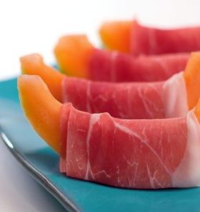 As an appetizer for a party, friends of mine used to take small pieces of proscuitto and melons with a bit showing on both sides. Then, they would wrap the proscuito around the melon and secure with toothpicks.