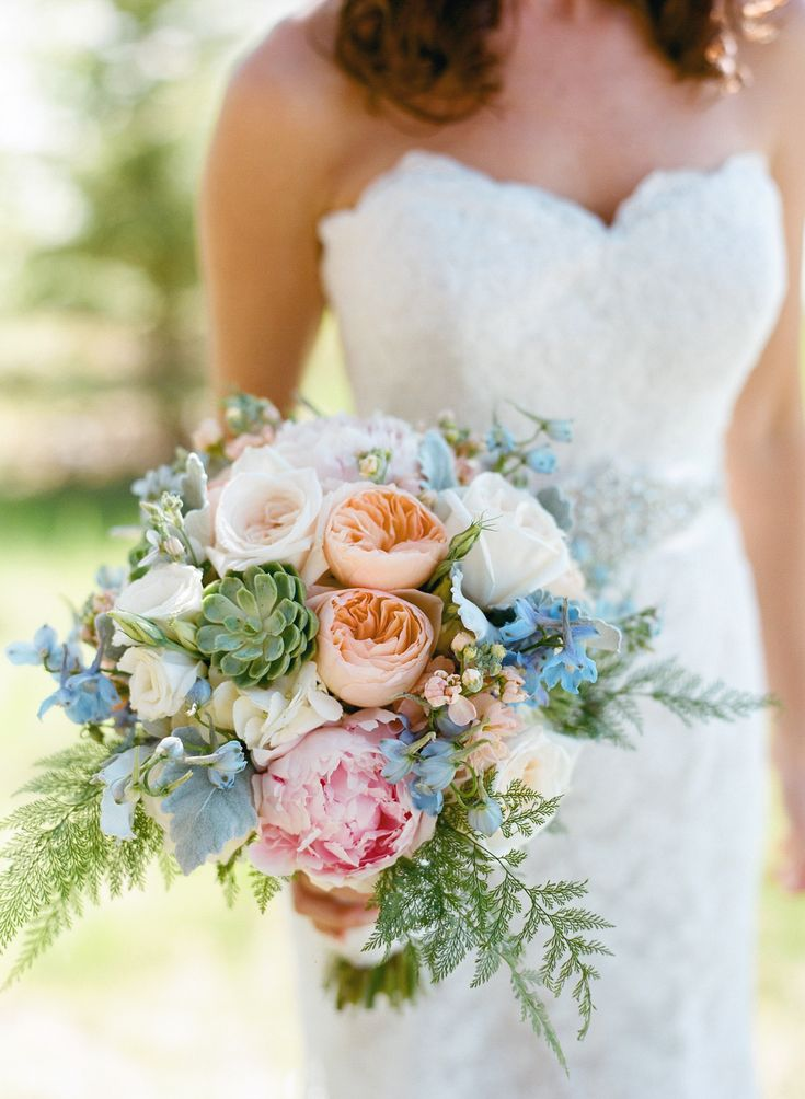 Peach garden roses, pale pink peonies, ferns, succulents and light blue delphinium.