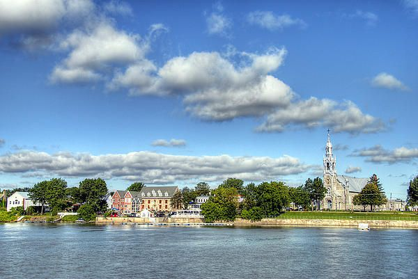 The older section of Beloeil, also known as Saint-Mathieu, as seen from the east bank of the Richelieu River. The fluffy clouds were very prominent that day and needed to be a focal point of this photo. The church, Eglise Saint-Mathieu, was built in 1895 and is the third church built on that site. The two previous churches, built in 1787 and 1817 burned and had to be rebuilt. #beloeil, #church, #clouds