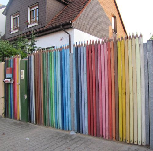 Couloured pencil barrier by (Finnish) Jonna Pohjalainen, Latvia | This rainbow coloured fence might be a creative idea for your garden or backyard. Could also be fun as street art. Click to see pictures of giant tree trunk pencils.