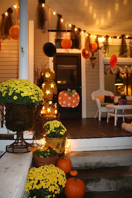 love the whimsy of this front porch....cute swirly designs & stars on pumpkins & string of lights with decor hanging from them.