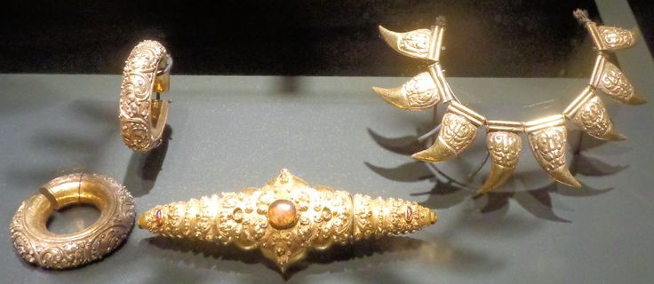 Dit zijn gouden sieraden uit Java. Rechts is een halsketting met acht versierde elementen in de vorm van tijgerklauwen. Mogelijk bestond het oorspronkelijk uit tien klauwen, twee maal vijf, zodat het de voorpoten van de tijger voorstelt. De tijgerklauwen dienden als sieraden voor beelden van hindoegoden als Krishna en Manjushri. Daarom zijn deze sieraden ook vrij zeldzaam.