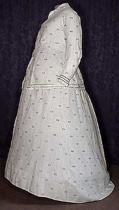 1860's 3 Piece Faille Maternity Dress   Rare 1860's 3 Piece Faille Maternity Dress A very fine and elusive post Civil War three piece lady's maternity ensemble. Absolutely lovely! A very pretty printed pattern of white roses within green medallions with sprigs scattered among them.   The long fitted tunic has a four shell button front closure that is opened from above the waistline down. A classic V back construction, modified coak sleeves and trimmed at the collar, cuffs and hem with bands…