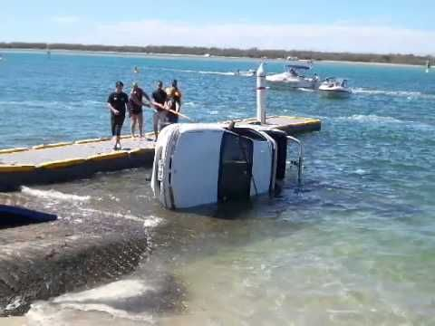 Lady backs car into water with boat and trailer
