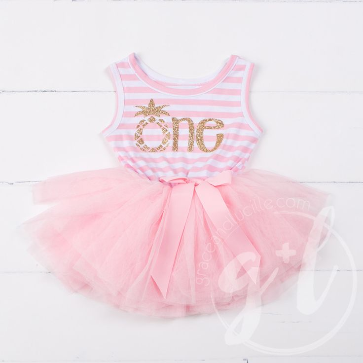 """A tropical dress for her first birthday! Super sparkly gold lettering with pineapple graphic and lettering spells out """"one."""" Premium cotton/spandex sleeveless top with attached extra-full tulle tutu a"""