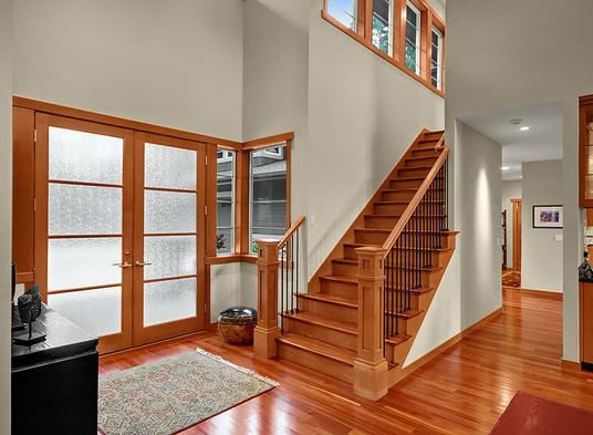 This 2 story foyer features wood stairs and handrail with for House plans with stairs in foyer