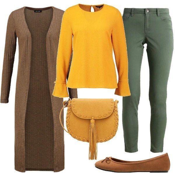 Il cardigan marrone melange è extra lungo e confortevole. Sotto, la blusa gialla con scollo tondo, chiusa con un bottoncino sul retro, ha il fondo delle maniche leggermente scampanato e con i laccetti. I pantaloni verdi vestono aderente. Ai piedi le ballerine marroni, mentre la borsa a tracolla con nappina è color senape.