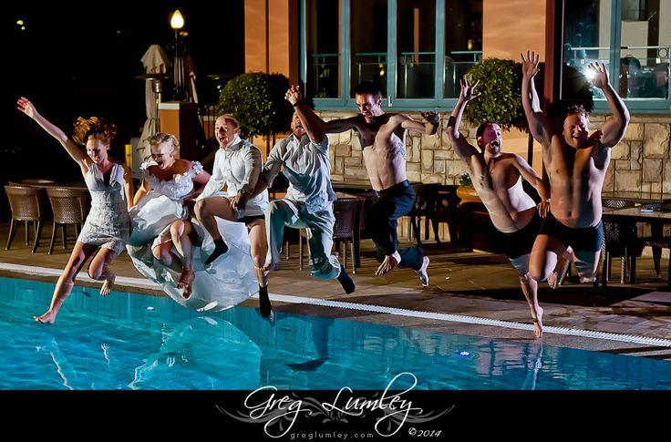 Bridal party jumping in pool.  Wedding photos taken at night.  Night shoot by wedding photographer Greg Lumley.