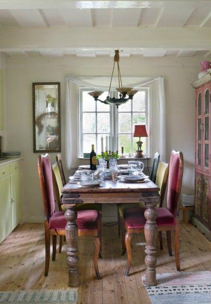Kring det rejäla köksbordet från Indien samsas udda stolar fyndade på auktion och loppis. Lampor, skåp och spegel från Raja.