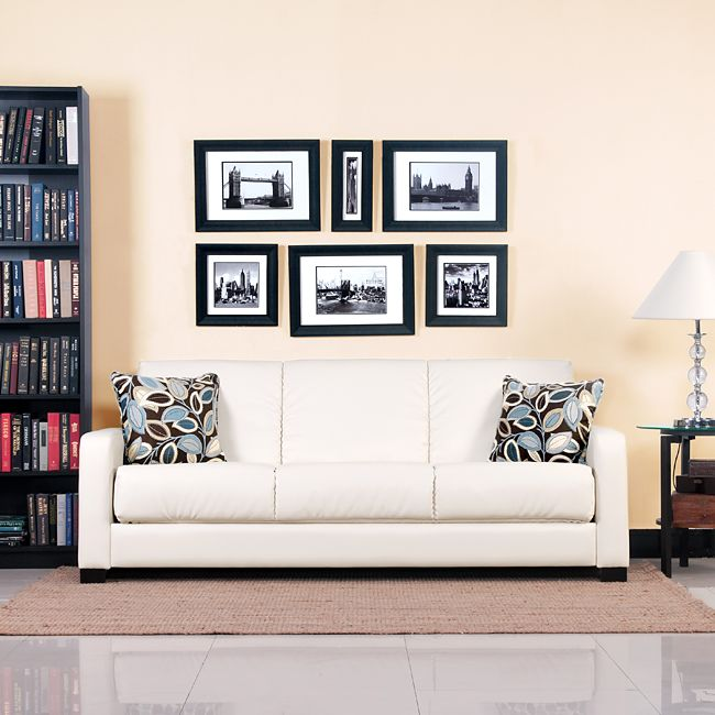 Comfortable and stylish, the transitional Portfolio Trace Convert-a-Couch futon sofa features squared arms and converts into a full size bed with the touch of a hand. The futon sofa is covered in a cream renu leather and works well in any decor.