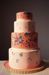 Tiers of pale pink and peachy-orange, topped with a hand-painted floral motif, have a sweet, rustic charm.
