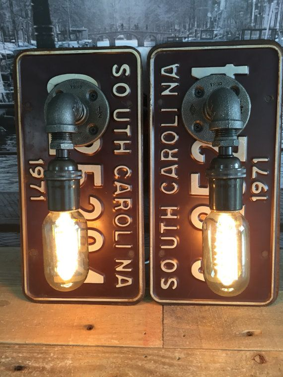 Steampunk Industrial 1971 South Carolina License Plate Pipe Lamp Sconce Pair  Featured is a pair handmade pipe lamp sconces mounted on 1971 South Carolina License Plates. Plates are brown with white paint and are in good condition and a matching set. Each are constructed with 1/2 inch black steel pipe and one antique brass light socket. Each plate is mounted to a wood backing to increase rigidness. Each light socket can handle up to 250 watts and features 12 inches of electrical cord…