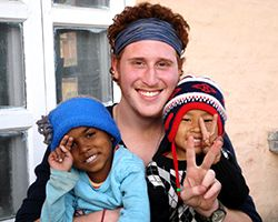 Orphage quests...Unitedplanet.org A young man and two children hold up the peace sign while smiling