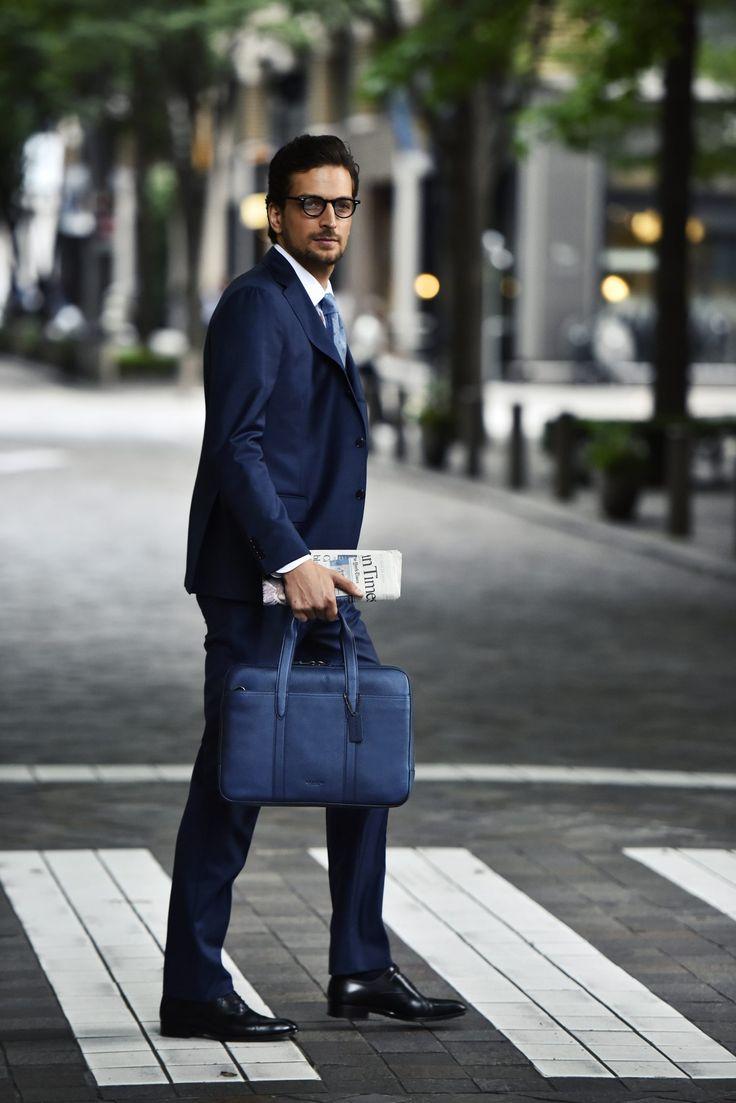 「COACH」といえば、デザイン性と耐久性を備えたバッグを展開するニューヨークを代表する高級皮革製品ブランドだ。元々は使い込むほどに手になじむという野球グローブに使用されている革を研究し、バッグに応用したのがはじまり。昨今では女性人気が著しいためレディースブランドとの認識をしている方も少なくないかもしれないが、元々は紳士をメインターゲットに始動したブランドであることはおさえておきたい。今回はそんな「COACH」のメンズバッグを洗練されたスーツスタイルと共に紹介。 ブラウンチェックスーツスタイル × COACH さりげなくチェックパターンが施されたブラウンのウールスーツを基軸に、ストライプシャツ、ペイズリータイ、シューズやメガネに至るまでブラウンで統一した洗練コーディネート。自然な光沢感が魅力のカーフレザーのメトロポリタン トートを合わせることで落ち着いたブラウンスーツスタイルにほどよくカジュアル・スポーティーな印象が加わり洒脱なスタイルが完成。 デ ペトリロのブラウンチェックウールスーツ16万6000円(ビームス ハウス 丸の内…