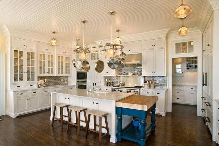 www.homestratosphere.com Cozinha branca luxuosa com piso de madeira com um toque de cor fornecido por umbloco de açougueiro portátilazul brilhante.As características notáveis incluem os acessórios do armário, os gabinetes de rosto de vidro eo rack de panela.