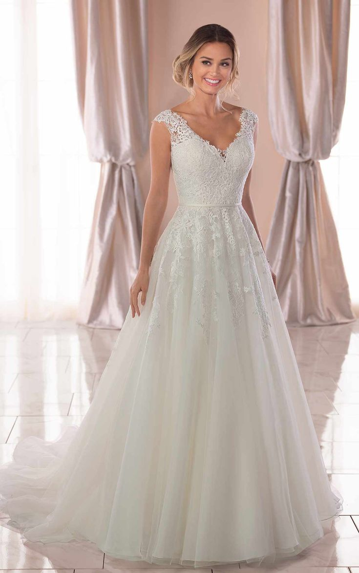 Traditional yet refined, this vintage A-line wedding dress has a soft train feat…
