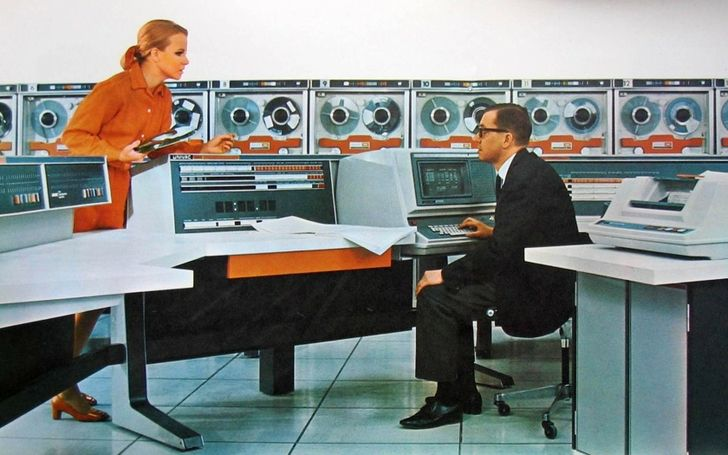 Univac ... The corporate color of orange is prominent in this computer room photo, even to the color of her dress, and her shoes!