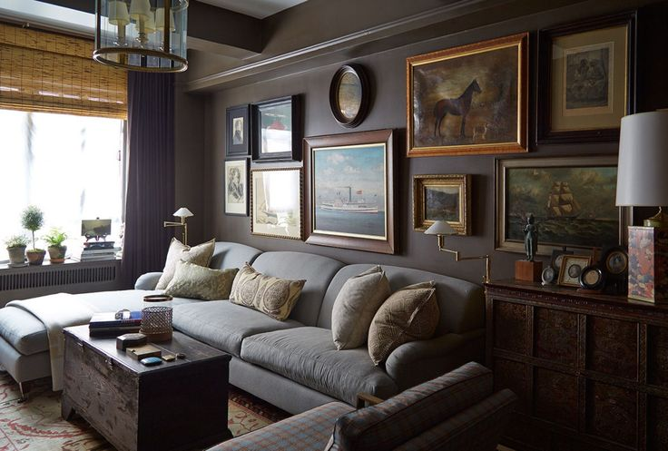 Matte chocolate brown walls, a large brass lantern, tailored settee, stick roman shades, and a lovely gallery wall make for a classic yet comfortable sitting room on Sutton Place by Robert Brown.