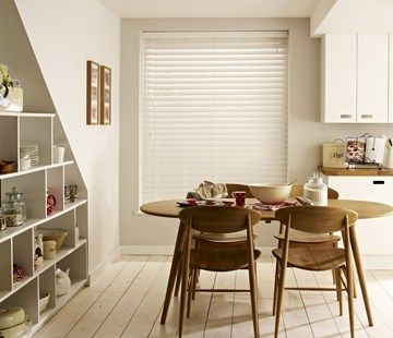 White wooden venetian blinds make an attractive window finish in this attractive white kitchen. #interiordesign #kitchens #blinds
