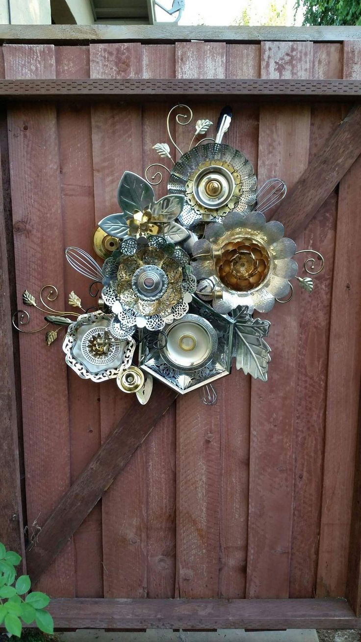 Funky junky fence garden art made from old metal serving dishes and other scraps