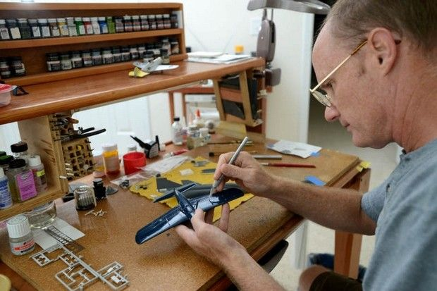 Mike Allen, retired Navy Master Chief Petty Officer, fits custom parts on a OS2U Kingfisher 1/48th scale model Thursday at his work bench.