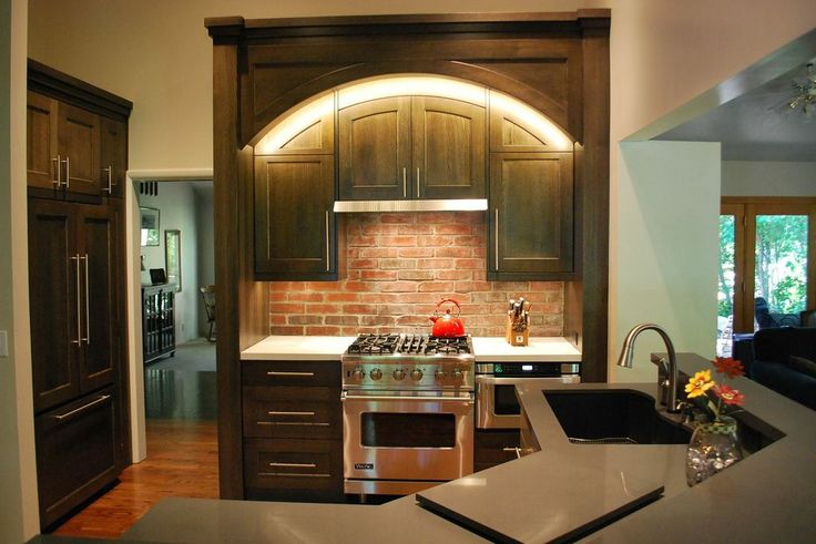 Beautiful dark custom cabinetry. Love the arch and the lights over the viking range. Anvil Cabinets www.anvilcompanies.com  #kitchencabinets #darkwood #cabinets #vikingappliances #traditional
