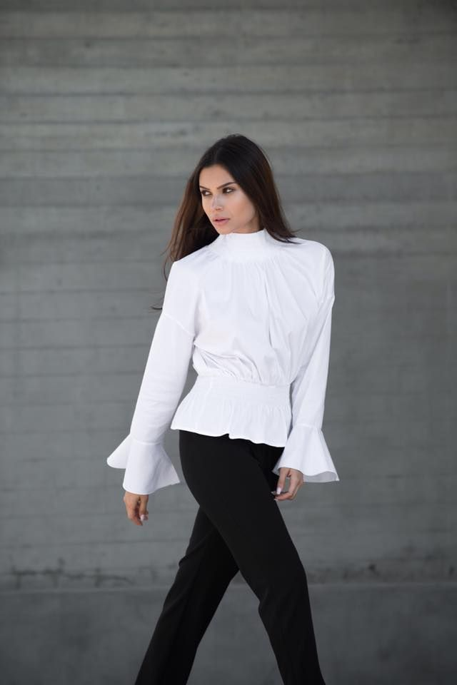 Shirt with gathered neck and waist. Long bell sleeves and round raised neck. Back button fastening. 79% Cotton. 18% Polyamid. 3% Elastane.