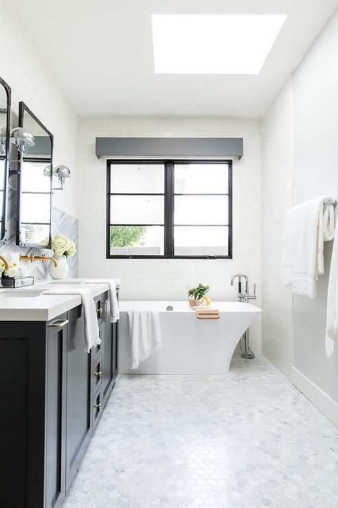 Charming white and gray contemporary master bathroom is illuminated by natural light streaming in through a skylight located above marble hex floor tiles.