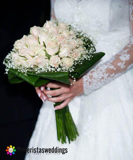Μία νυφική ανθοδέσμη με ιβουάρ τριαντάφυλλά, λευκές πέρλες και γιψοφύλλη.