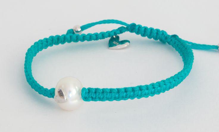 Pulsera tejida en macramé de color azul con incrustación en forma de corazón sobre perla blanca.