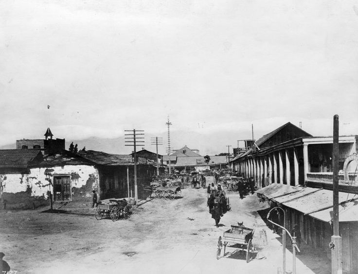"""ca. 1882)^ - Looking north toward the Plaza along """"Calle de los Negros,"""" which became part of Los Angeles Street. The Lugo House is seen with hipped roof and dormer windows, and, on left, is the cupola and flag pole of Fire Station 38.   Historical Notes  There was no area more colorful than Los Angeles's Calle de los Negros, a short dirt thoroughfare located just off the eastern edge of the historic Plaza and considered to be the center of the town's """"red light"""" district. Saloons, ..."""