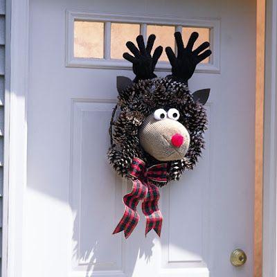 Couronne de porte avec des pommes de pin, un bonnet de laine claire, des gants marron, un pompon rouge et deux blancs, un ruban, le tout monté sur une arceau métallique