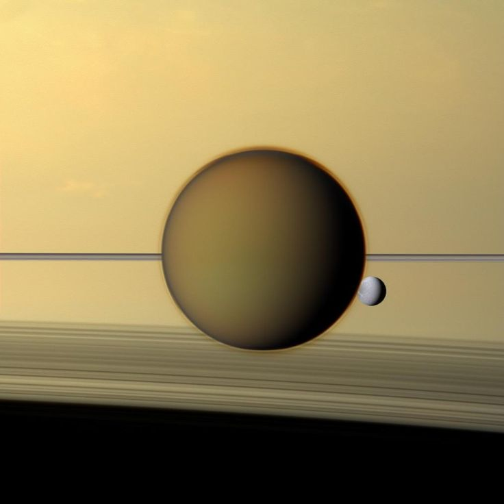 Titan and Dione against the larger background of Saturn.  The rings, though incredibly wide, are also incredibly thin, and are seen edge on as a thin line crossing behind Titan.  Titan looks fuzzy because it has a thick, hazy atmosphere.Nasa Cassini, Saturn Moon, Solar System, Holiday Treats, Cassini Spacecraft, Final Frontier, Largest Moon, Moon Titanic, The Moon