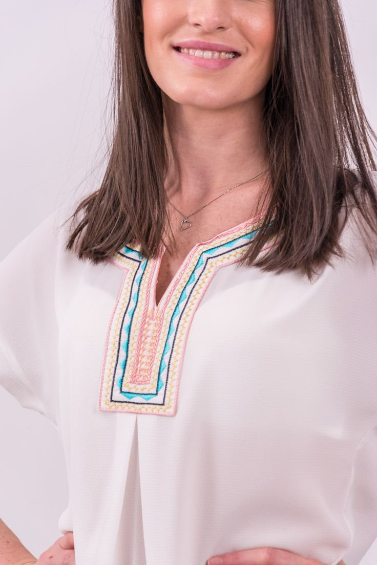 Bluză din material texturat fin, vaporos, de culoare albă cu decolteu în V. Este acccesorizată în partea frontală, în zona decolteului cu broderie decorativă. Mâneci scurte, neaccesorizate. Terminație asimetrică, rotunjită.