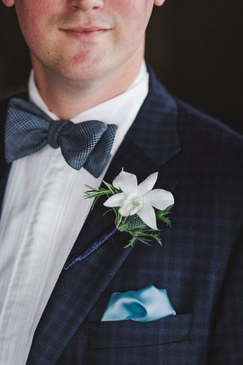 Chic white orchid boutonnière and navy blue bow tie