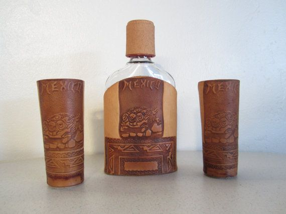 A three piece matching barware set of two shot glasses and a flask. They each have a hand tooled leather case featuring the word Mexico, a tortoise/turtle, and southwestern designs. The leather case laces up the back of each piece. The flask and shot glasses are a heavy glass, the top to the flask is plastic.  Measurement:  Shot Glasses: 4 inches tall and 1 1/4 inches wide.  Flask: 6 3/4 inches tall and 1 1/4 inches wide