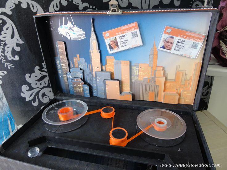 """Gros plan sur l'ouverture de l'urne """"Mission impossible""""... Effet de la ville de New York en relief et d'un vieux magnétophone."""