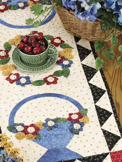 Serendipity Table Runner  Three-dimensional flowers made from fabric yo-yos fill the baskets on this colorful table runner.  Free Download
