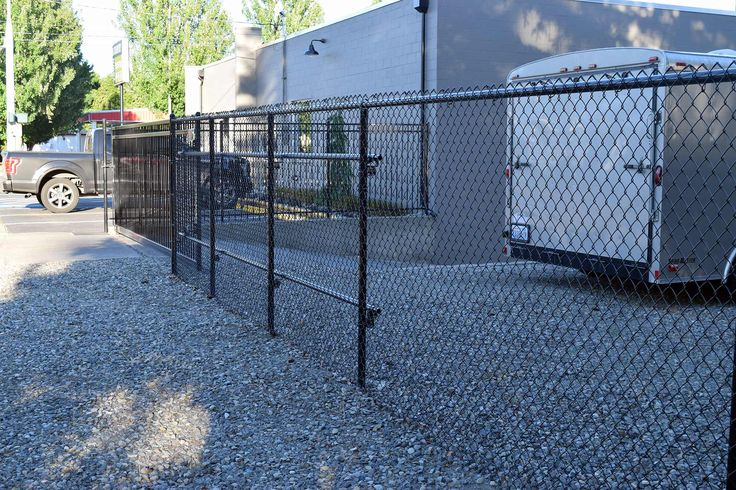 The chain-link fence we installed complements the iron gate and fence from the front of the property. It's still durable and secure, but reduced cost considerably over a full-perimeter iron fence.